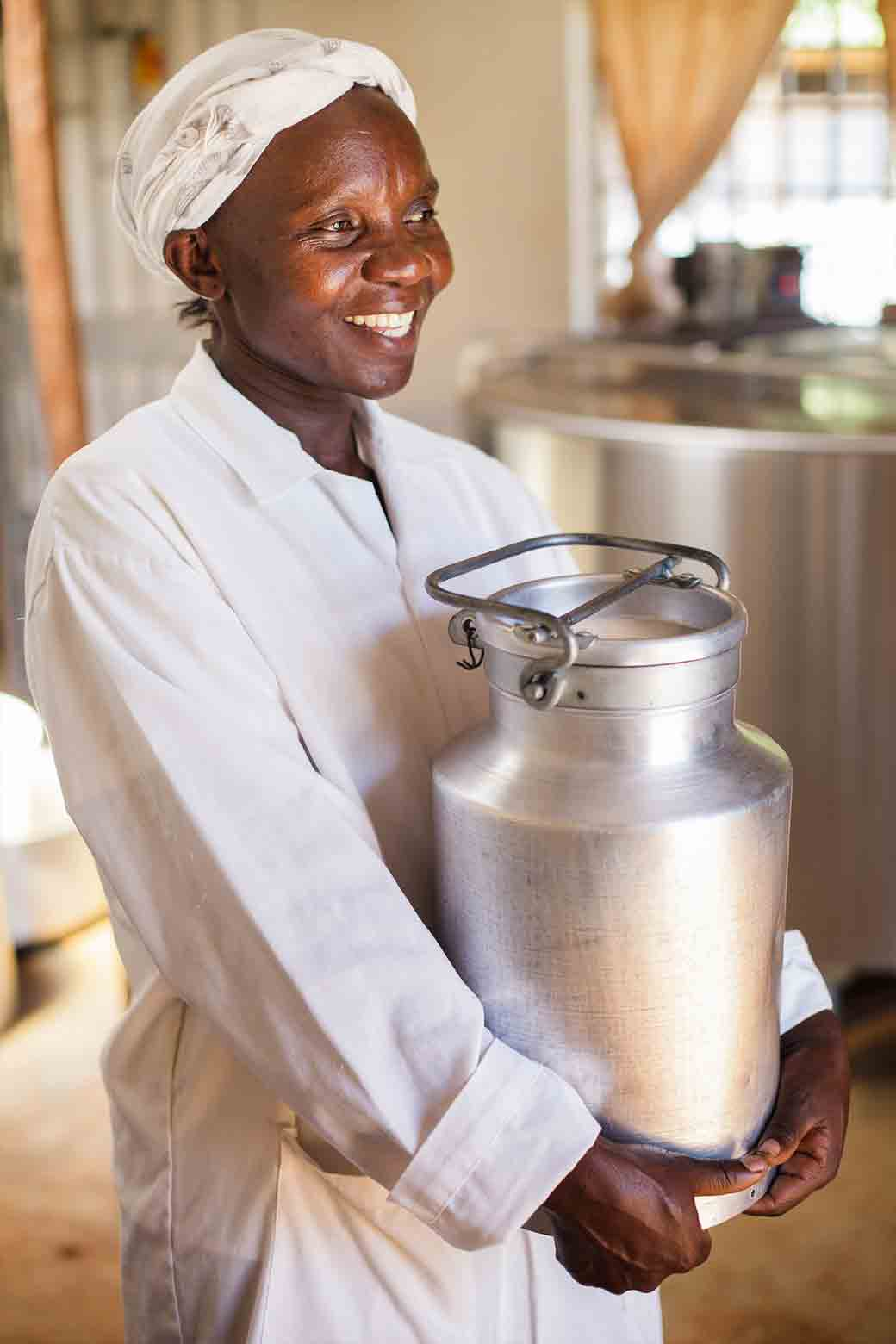 A member of the Ahero Dairy Farmers cooperative in Kisumu, Kenya carries fresh milk that will be turned into yogurt for sale through the cooperative's store.