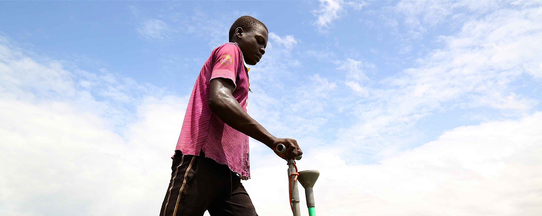Mamadou uses the mechanical applicator to easily apply targeted fertilizer in his father's rice field in Mali.