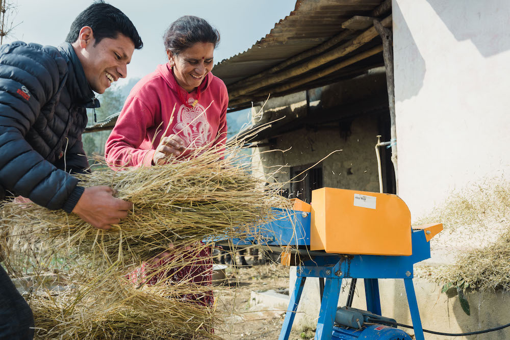 Radhika Bolakhe gets a hand with her chaff cutter from a local private sector partner